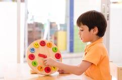 Tiempo de aprendizaje del niño pequeño con el juguete del reloj del educationa del montessori Fotos de archivo