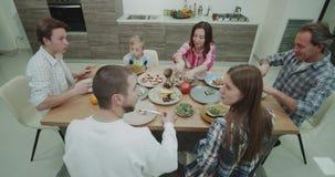 Tiempo de cena en una porción grande y la consumición de la opinión de la familia también de una comida comida hermosa y colorida metrajes