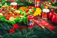 Tiempo de cena de la tabla de la Navidad con las carnes asadas, velas Día de la acción de gracias del fondo Fotografía de archivo libre de regalías