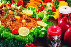 Tiempo de cena de la tabla de la Navidad con las carnes, las velas y décor asados del Año Nuevo Día de la acción de gracias del  Foto de archivo