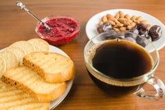 Tiempo de desayuno, taza de café con las tostadas, atasco de frambuesa, fechas, almendras en la tabla de madera Imágenes de archivo libres de regalías