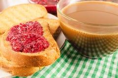 Tiempo de desayuno, taza de café con leche y tostadas con el atasco de frambuesa en servilleta Fotos de archivo libres de regalías