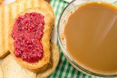 Tiempo de desayuno, taza de café con leche y tostadas con el atasco de frambuesa en servilleta Imagen de archivo libre de regalías