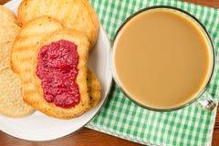 Tiempo de desayuno, taza de café con leche y tostadas con el atasco de frambuesa en servilleta, visión superior Fotos de archivo