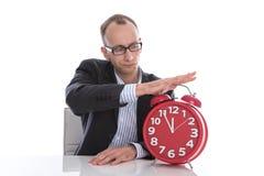 Tiempo de detención del hombre de negocios en el reloj rojo aislado en el backgro blanco Foto de archivo