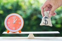 Tiempo de la balanza y concepto de la inversión de los ahorros del dinero fotografía de archivo