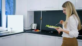 Tiempo de la comida de la gente feliz con la ensalada en placa y la bifurcación en manos en sitio en casa almacen de metraje de vídeo