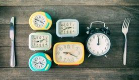 Tiempo de la comida, hora de comer concepto Relojes con la cuchara y la gente en el wo Fotografía de archivo libre de regalías
