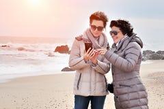 Tiempo de la familia Internet de la ojeada de la hija y de la madre en el smartphone, charlando en línea en la playa imagenes de archivo