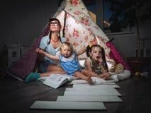 Tiempo de la familia: madre y ni?os de hermanas en el juego oscuro en casa en una tienda hecha en casa de los ni?os fotos de archivo