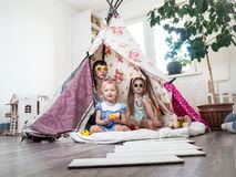 Tiempo de la familia: La mam? y algo de los ni?os de las hermanas juegan en casa en una tienda hecha en casa de los ni?os fotos de archivo