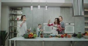 Tiempo de la familia para los cuatro miembros hermosos en el cocina moderna que hace burbujas y tener un buen humor feliz 4K almacen de video