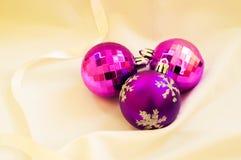 Tiempo de la Navidad Bolas púrpuras de la Navidad en una tela blanca Imágenes de archivo libres de regalías