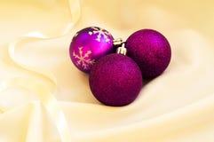 Tiempo de la Navidad Bolas púrpuras de la Navidad en una tela blanca Imagen de archivo
