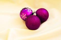 Tiempo de la Navidad Bolas púrpuras de la Navidad en una tela blanca Imagen de archivo libre de regalías