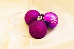 Tiempo de la Navidad Bolas púrpuras de la Navidad en una tela blanca Fotos de archivo libres de regalías