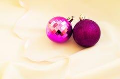 Tiempo de la Navidad Bolas púrpuras de la Navidad en una tela blanca Fotografía de archivo libre de regalías