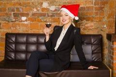 Tiempo de la Navidad en oficina Mujer de negocios rubia hermosa joven en el sofá de cuero Concepto del asunto Fotos de archivo libres de regalías