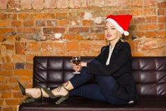 Tiempo de la Navidad en oficina Mujer de negocios rubia hermosa joven en el sofá de cuero Concepto del asunto Imagen de archivo libre de regalías