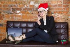 Tiempo de la Navidad en oficina Mujer de negocios rubia hermosa joven en el sofá de cuero Concepto del asunto Foto de archivo libre de regalías