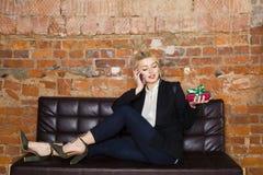 Tiempo de la Navidad en oficina Mujer de negocios rubia hermosa joven en el sofá de cuero Concepto del asunto Fotografía de archivo libre de regalías