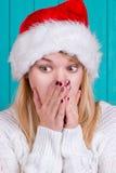 Tiempo de la Navidad Mujer joven que lleva el vestido rojo del sombrero de Papá Noel en fondo azul Fotografía de archivo