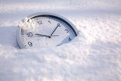 Tiempo de la nieve, un reloj en la nieve Foto de archivo libre de regalías
