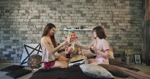 Tiempo de la pizza para un grupo de partido casero en el dormitorio moderno, señora de las señoras de los amigos que sostiene tre almacen de metraje de vídeo