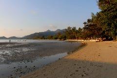 Tiempo de la puesta del sol en la isla con el fondo del cielo azul y de la montaña fotos de archivo