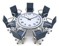 Tiempo de la reunión - mesa redonda con una cara de reloj grande Fotografía de archivo