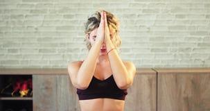 Tiempo de la yoga para un primer de la mujer ella tiene un rato de la meditación delante de la cámara que mira la sensación recta almacen de metraje de vídeo