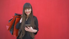 Tiempo de las compras, la señora feliz utiliza smartphone y sonríe con las bolsas de papel en fondo rojo almacen de video