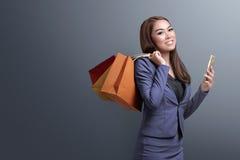 Tiempo de las compras, mujer asiática con el smartphone que sostiene los panieres Imagen de archivo