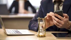 Tiempo de medición del reloj de arena, hombre de negocios usando el teléfono móvil, dilación imagen de archivo