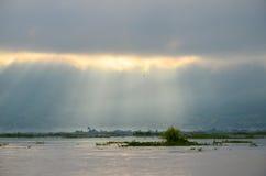 Tiempo de niebla de la mañana con los rayos del sol que brillan a través de las nubes sobre el lago Fotografía de archivo libre de regalías