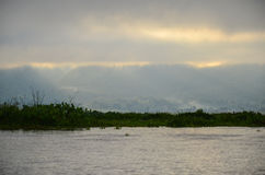 Tiempo de niebla de la mañana con los rayos del sol que brillan a través de las nubes sobre el lago Foto de archivo