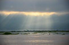 Tiempo de niebla de la mañana con los rayos del sol que brillan a través de las nubes sobre el lago Fotos de archivo libres de regalías