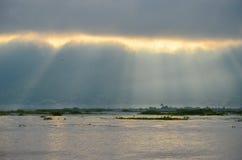Tiempo de niebla de la mañana con los rayos del sol que brillan a través de las nubes sobre el lago Fotos de archivo