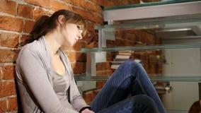 Tiempo de observación de la mujer joven que se sienta y que espera en el reloj metrajes