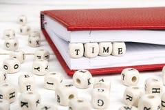 Tiempo de palabra escrito en bloques de madera en cuaderno rojo en la madera blanca Foto de archivo libre de regalías