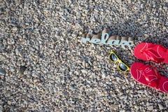 Tiempo de relajación en la playa con las gafas de sol y las chancletas fotografía de archivo