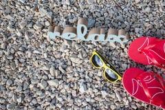 Tiempo de relajación en la playa con las gafas de sol y las chancletas fotos de archivo