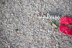Tiempo de relajación en la playa con las gafas de sol y las chancletas fotos de archivo libres de regalías