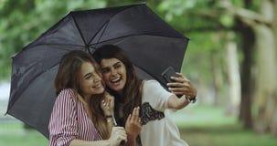 Tiempo de Selfie para dos señoras el día de la lluvia que toma imágenes usando un teléfono, debajo del paraguas 4K almacen de metraje de vídeo