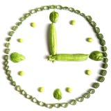Tiempo del almuerzo Dieta vegetariana de verduras bajo la forma de relojes, cebollas verdes, albahaca y guisantes aislados en un  foto de archivo libre de regalías