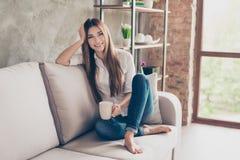 Tiempo del café Señora joven encantadora feliz sonriente en el sofá en h Imágenes de archivo libres de regalías