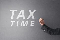 Tiempo del impuesto de la escritura de la mano de la persona del negocio con la pluma Imágenes de archivo libres de regalías