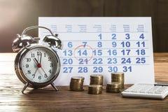Tiempo del impuesto en el despertador con las monedas fotografía de archivo