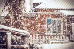 Tiempo del invierno de las nevadas en pueblo con los copos de nieve y la ventana vieja de la casa Foto de archivo libre de regalías