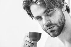 Tiempo del mejor para comer su taza de caf? El hombre del aspecto atractivo del individuo disfruta de cierre preparado fresco cal foto de archivo